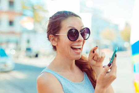Excited funny young woman raising her finger about to push the button on her cell phone looking at you camera