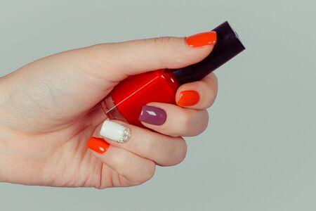 Nail Polish. Art Manicure. Multi-colored Nail Polish. Beauty hands holding red bottle. Stylish Colorful Nails