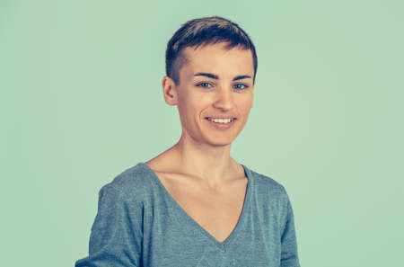 Close up portrait of a smiling young woman with short hair and grey shirt isolated light green background wall