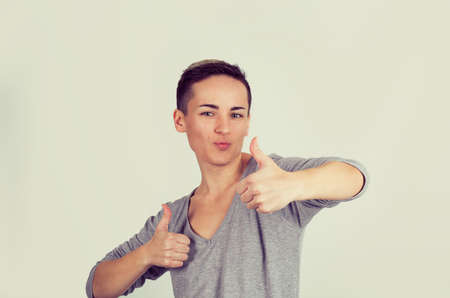 Closeup portrait young, short hair woman student being excited giving showing thumbs up hand gesture isolated light yellow background. Positive human emotion face expression feeling sign symbol