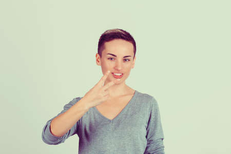 Portrait lovely happy teenage girl showing victory or peace sign isolated on green grey wall background. Positive face expression emotion body language 免版税图像