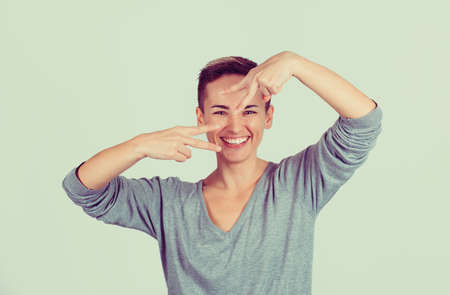 Portrait lovely happy woman showing victory or peace sign gesture isolated on green gray wall background. Positive face expression emotion body language 免版税图像