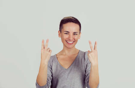 Portrait lovely happy woman showing victory or peace sign gesture isolated on light gray wall background. Positive face expression emotion body language 免版税图像 - 151030652