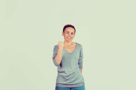 Closeup portrait happy successful student, woman winning, fist pumped celebrating success isolated on light green wall background. Positive human emotion facial expression. Life perception achievement