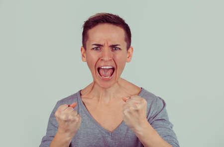 Angry young woman with fists up screaming isolated on bright green gray wall background. Negative human emotions feelings face expression Stok Fotoğraf