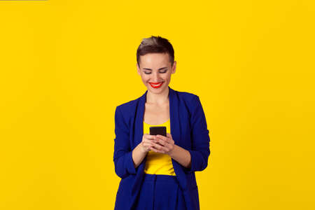 Happy young woman holding using new smartphone connected browsing internet worldwide isolated on yellow wall background. 4g data plan provider