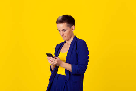 Phone addiction. Interested addicted business woman girl looking to her phone gadget internet isolated yellow background wall. 免版税图像