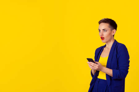 Shocked business woman with phone looking to the side copy space isolated yellow background wall. Business attire formal blue suit, short hair, red lips