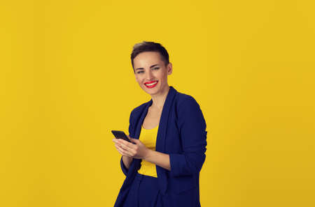Closeup woman hands holding using smart mobile phone looking at you camera smiling isolated on yellow wall. New generation technologies phone addiction concept. Customer service provider relationship