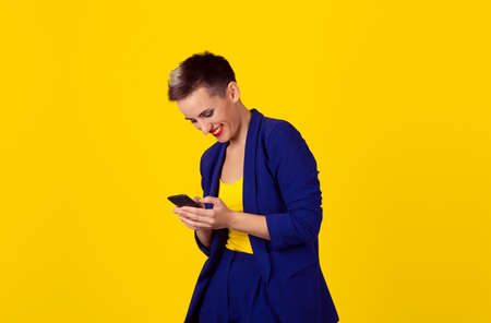 Happy chat. Closeup portrait, happy, brunette girl, smiling, looking at company cell phone, isolated yellow background. Facial expression, reaction. Business woman sending text message from her mobile