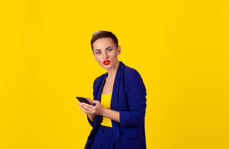 Closeup portrait frustrated shocked woman hands holding, using smart, mobile phone isolated yellow background. New generation technologies, people phone addiction concept.
