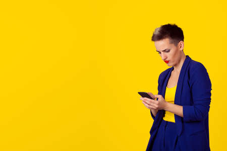 Portrait young angry woman unhappy, annoyed by something, someone on her cell phone texting, receiving bad sms text message news isolated yellow wall background. Human face expression emotion reaction