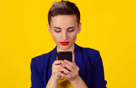Serious business woman looking texting at phone isolated yellow background wall. Short hair, formal wear 免版税图像