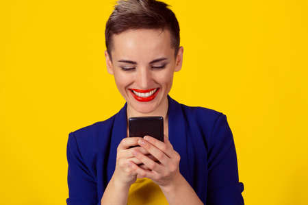 Staying connected. Happy young woman looking at her mobile phone and smiling pumping fist celebrates success isolated yellow wall background. Excited laughing girl receiving good news on cell phone