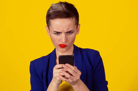 Closeup portrait upset skeptical unhappy serious woman looking at texting on phone displeased with conversation isolated on yellow background. Negative human emotion face expression feeling 免版税图像