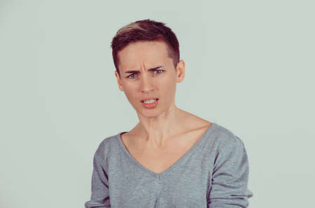 Closeup portrait young serious angry grumpy woman isolated on gray wall background. Negative human emotion feelings face expression reaction