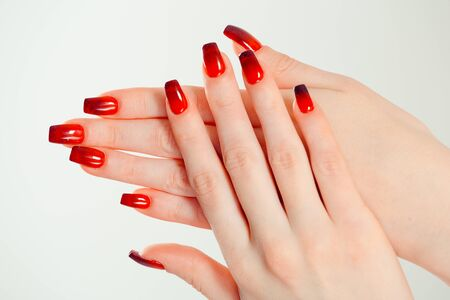Nail Polish. Art Manicure. Modern style red black gradient Nail Polish. Beauty hands with Stylish Colorful trendy Nails isolated white background