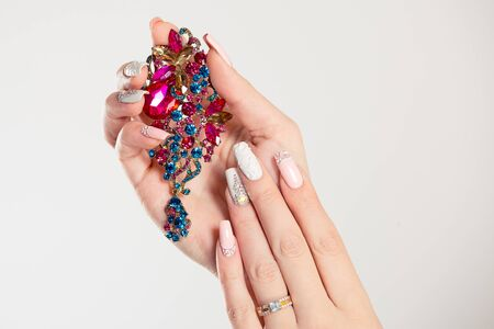 Closeup nail polished pastel multicolored long nails coral pink, white with crystals, hand holding perfume pink blue green broach jewel isolated on white background. Classic wedding bride nails design Stok Fotoğraf