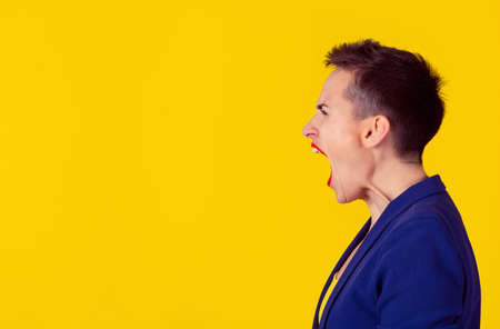 Side view portrait angry woman screaming, wide open mouth, hysterical isolated yellow wall background. Negative human face expressions, emotion, bad feelings reaction. Conflict, confrontation concept