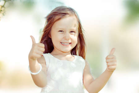 The little girl happy toddler kid showing thumbs up gesture with hands,  outdoors green tree park on background. Funny picture Standard-Bild