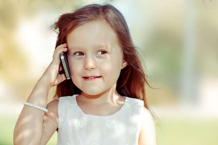 Girl talking on phone. Beautiful, attractive little girl having a conversation with friends on cellphone isolated outdoors background. Positive human face expression emotion. Kids & technology concept 免版税图像