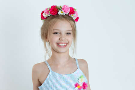 Close up portrait little cheerful Girl Smiling in the Camera  in wreath of flowers isolated white grey background wall 免版税图像