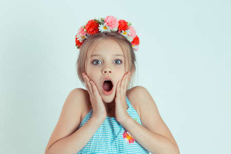 Wow. Beautiful girl excited holding her mouth open, hands on cheeks. Shocked surprised stunned. Positive emotion. Closeup portrait of Caucasian kid model with floral headband on light blue background
