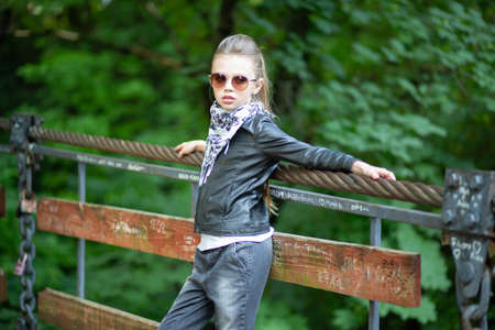 Fashion girl poses outside. Closeup portrait, confident, successful, beautiful attractive girl, kid posing with sunglasses on a bridge isolated outdoors in the nature background. Positive emotion Standard-Bild