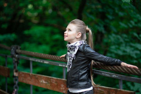 A fashion girl looking up daydreaming. Closeup portrait, confident, successful, beautiful attractive girl, kid posing with sunglasses on a bridge on outdoors in the nature background. Positive emotion Standard-Bild