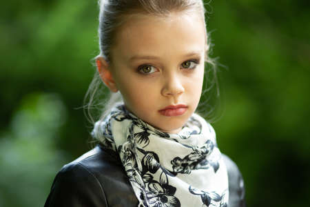 A fashion girl poses outside. Closeup portrait, confident, successful, beautiful attractive girl, kid posing on a bridge isolated outdoors in the green nature background. Positive emotion