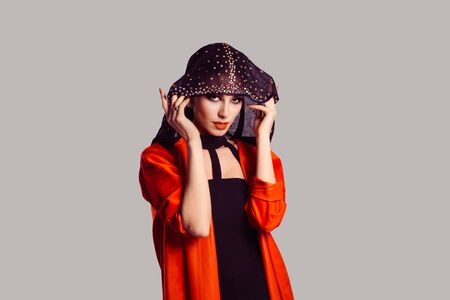 Beautiful shy muslim woman covering face with fashion veil isolated on grey gray wall background. Closeup portrait of young gorgeous bride. Studio shot. Woman in red portrait with black veil over face