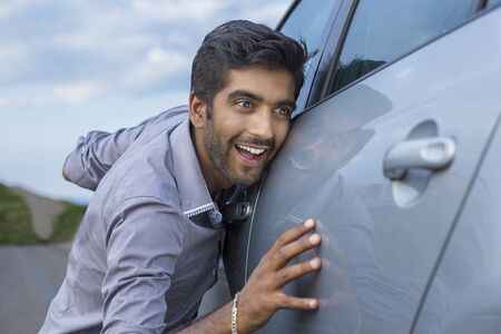 Happy excited young brunette italian man driver embracing petting his car outdoors. Green energy biofuel electric environment friendly new car concept.  Positive face expression human emotion reaction