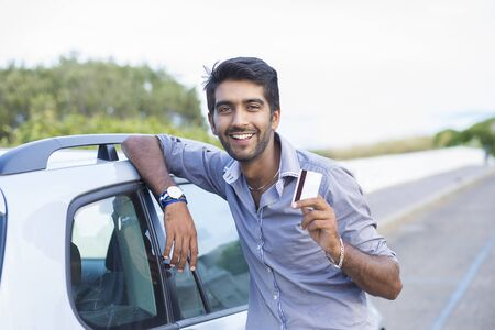 Happy smiling man standing near his new car showing credit card outdoors city road on background. Personal transportation auto purchase concept
