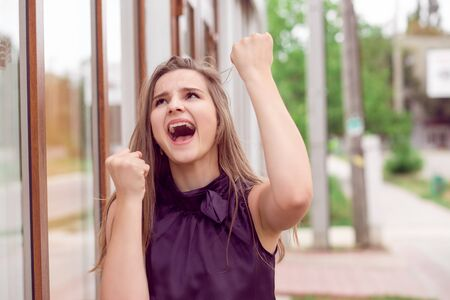 Lucky girl. Closeup portrait happy young woman happy exults pumping fists ecstatic isolated outdoors city store background. Celebrate success concept. Facial expression emotions feelings body language 스톡 콘텐츠