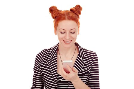 Texting. Closeup portrait cut out of a beautiful woman in her 30s holding looking at checking phone smiling happy wearing striped black white jacket with 2 buns up hairdo isolated on white background
