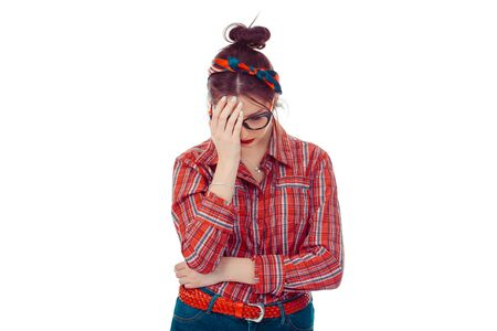 Sad woman hiding her face with hand looking down. Closeup portrait of a beautiful girl in red checkered shirt and jeans with retro bow on head isolated on pure white background. Mixed race, Hispanic.