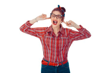 Woman covering ears shouting unhappy. Closeup portrait of a beautiful girl in red checkered shirt, jeans with retro bow on head isolated on pure white background. Mixed race, hispanic, caucasian model