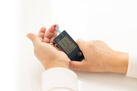 Hands of a person, woman or man self checking her, his diabetes and blood glucose monitor with digital pressure gauge, Glucometer. Healthcare and Medical concept. The blood sugar value is 11 very high