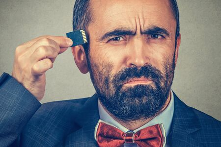 External memory needed concept. Portrait of interested bearded businessman wearing elegant jacket, red bow tie holding Micro SD card near head isolated on grey gray background. Human face expression