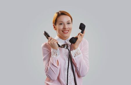 Sercretary. Happy woman holding, giving two telephones and laughing looking smiling at camera. Caucasian Business person, pink formal shirt, long redhead ginger hair isolated on light grey studio background
