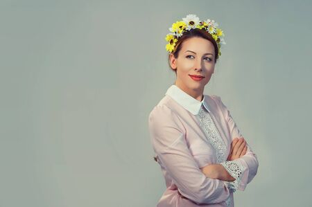closeup portrait, confident, successful, beautiful attractive young woman in floral crown from sunflowers, posing looking at camera with hands crossed fashion girl, isolated on grey gray background Foto de archivo