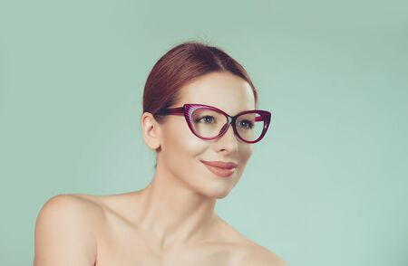 Showing new glasses. Closeup portrait young woman looking to the side wearing eyeglasses isolated on light green white wall background. Positive human emotion face expression