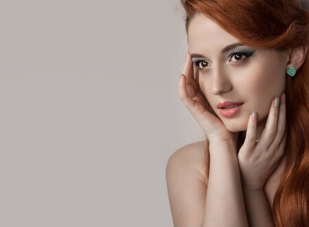 Beauty woman portrait with red hair. Beautiful redhead girl looking to side with hands touching face, sexy with pretty makeup. Multiracial Caucasian hispanic female beauty model isolated on gray beige background