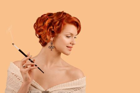 A beautiful young woman retro beauty girl up hairdo style posing in studio smoking a cigarette while standing in front of a orange background. Fashionable white wool dress natural make-up and tan skin