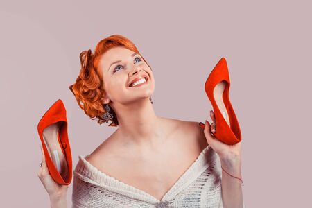 Girl with high heels. Closeup red head beautiful young woman pretty happy pinup girl in woolen dress holding heeled shoes laughing excited cheering gone crazy about new shoes, retro vintage hairstyle