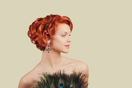Girl with peacock feathers dress. Closeup red head beautiful young woman happy pinup girl in dress made of peacock feathers, with curly updo retro vintage hairstyle looking to side smiling, posing