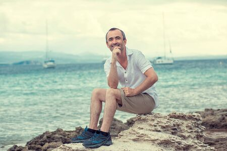 Smiling man sitting on the seashore coast by the sea, toothy smile middle age man multicultural mixed race, outdoors