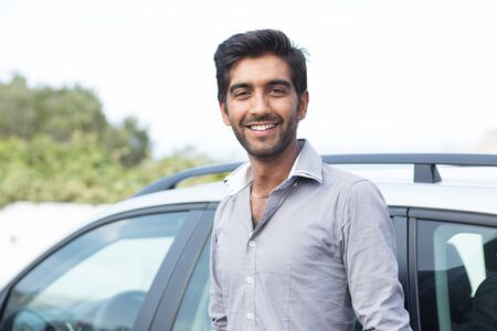 Happy man driver smiling standing by his new sport blue car isolated outside parking lot background. Handsome young man excited about his new vehicle. Positive face expression
