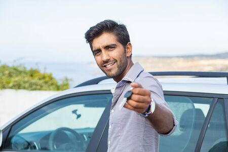 Closeup portrait happy, smiling, young man, buyer showing keys of his new car isolated outside dealership lot. Personal transportation, auto purchase concept