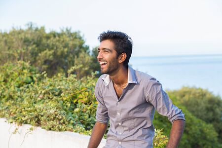 Laughing happy outside. Portrait of elegant Indian man in formal gray shirt outdoors smiling happily with arms crossed, near the lake sea with lots of copy space Foto de archivo